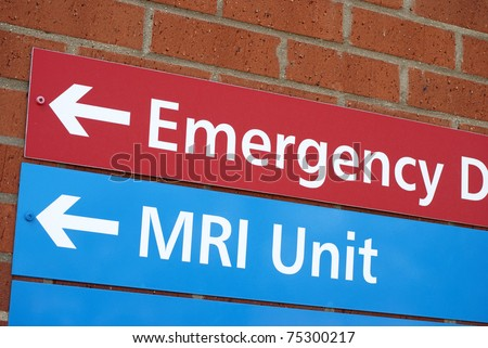 Sign of wall of hospital pointing to Emergency and MRI departments
