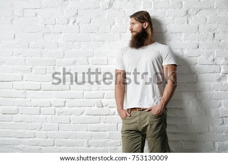 Trendy young bearded man in casual clothes standing against white brick wall - copyspace all around. #753130009