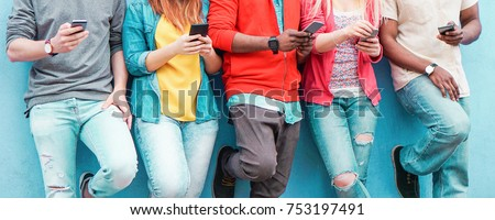Group of friends watching smart mobile phones - Teenagers addiction to new technology trends - Concept of youth, tech, social and friendship - Main focus on center hands  Royalty-Free Stock Photo #753197491