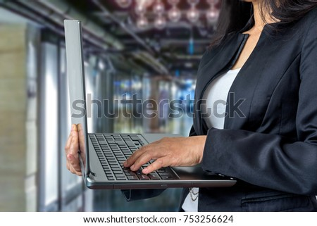 Businesswoman in formalwear using  notebook computer over office background / Business conceptual #753256624