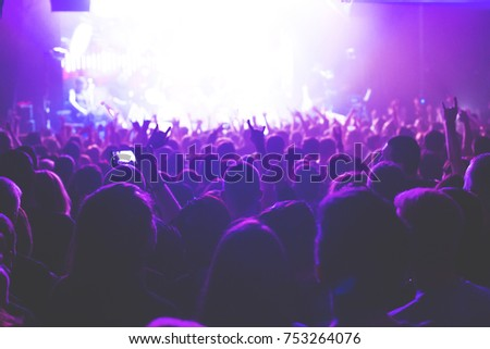 The audience watching the concert on stage in big concert club. #753264076