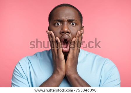 Headshot of stupefied astonished man wears casual t shirt, keeps hands on cheeks, says: Omg, I am tired of that. Surprised African American male realizes his fault. Ethnicity and emotions #753346090