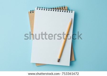 school notebook on a blue background, spiral notepad on a table #753361672