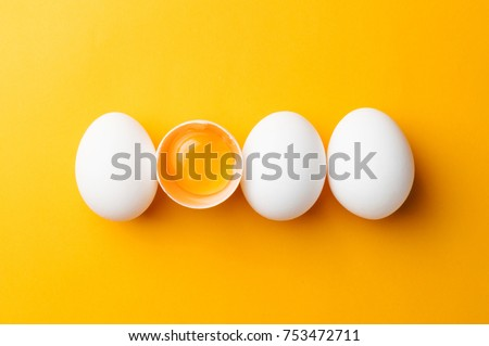 White eggs and egg yolk on the yellow background. Royalty-Free Stock Photo #753472711