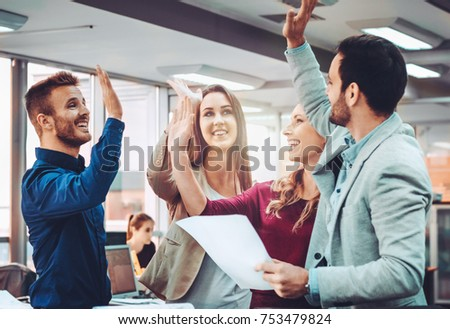 Group of business people celebrating their teamwork with a high five #753479824