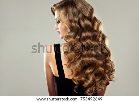 Brunette  girl with long  and   shiny curly hair .  Beautiful  model woman  with curly hairstyle. Care and beauty   Royalty-Free Stock Photo #753492649