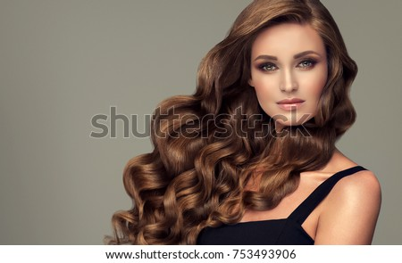 Brunette brown girl with long  and   shiny curly hair .  Beautiful  model woman  with curly hairstyle. Care and beauty   #753493906