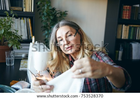 Picture of focused serious middle aged European woman sewing, using stitching machine at home, sitting at her workplace. Elderly female dressmaker holding fabric, scissors and measuring tape #753528370