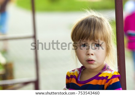 Little girl with funny expression on her face playing outdoors #753543460