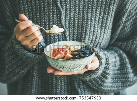 Healthy winter breakfast. Woman in woolen sweater eating rice coconut porridge with figs, berries, hazelnuts. Clean eating, vegetarian, vegan, alkiline diet food concept #753547633