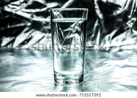 Glass of water on abstract silver background #753557392