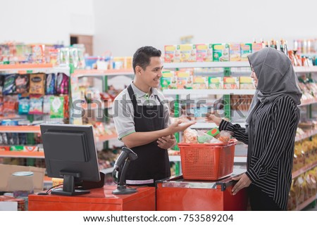 portrait of happy muslim woman paying her shopping with credit card in grocery store #753589204