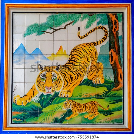 The colorful moseic decorated on the wall of a temple depicting the story of two tigers