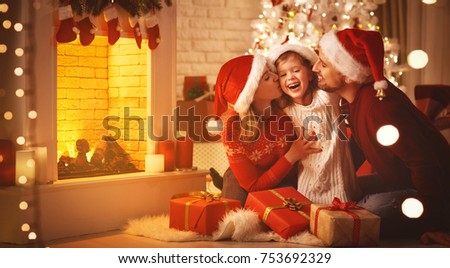 Merry Christmas! happy family mother father and child with magic gift near tree #753692329