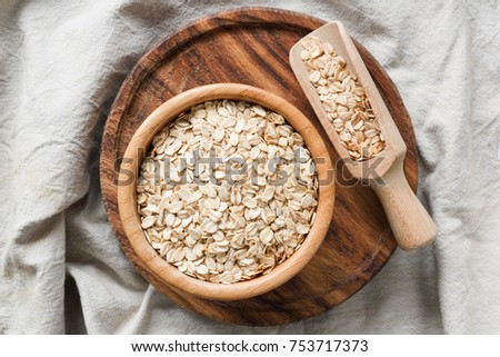 Rolled oats, organic oat flakes in wooden bowl on wooden background. Healthy lifestyle, healthy eating, vegan food concept #753717373