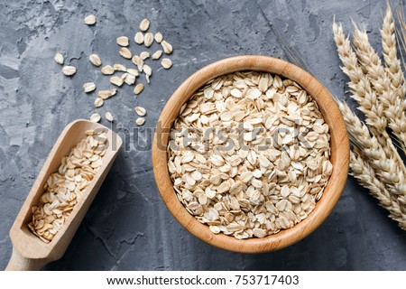 Rolled oats or oat flakes in wooden bowl and golden wheat ears on stone background. Top view, horizontal. Healthy lifestyle, healthy eating, vegan food concept #753717403