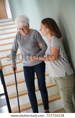Homecare helping elderly woman going down the stairs #753726238