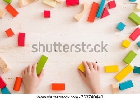 Top view on child's hands playing with colorful wooden bricks on white table background. Boy building with wooden constructor. Education concept #753740449