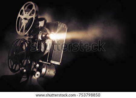 Movie projector on a dark background with light beam / high contrast image #753798850