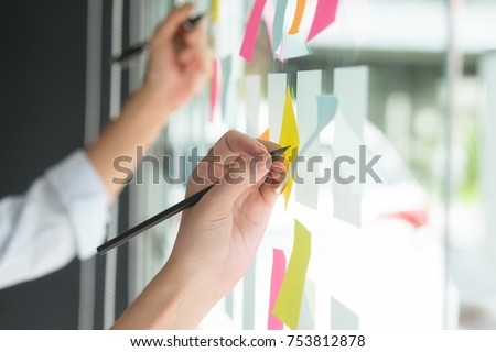 Hand writing paper note, sticky note on glass window with close up shot. Royalty-Free Stock Photo #753812878