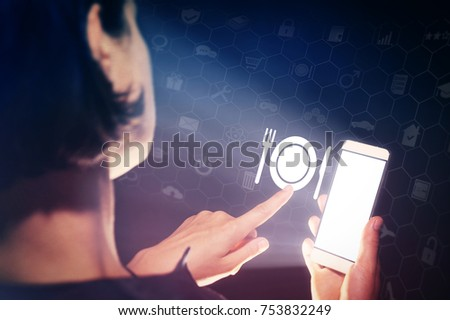 Image of a girl with a smartphone in hands. She presses on the  restaurant icon. Concept of modern technology in catering industry.