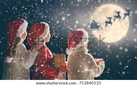 Merry Christmas and happy holidays! Cute little children with xmas presents. Santa Claus flying in his sleigh against moon sky. Kids enjoying the holiday with gifts on dark background.