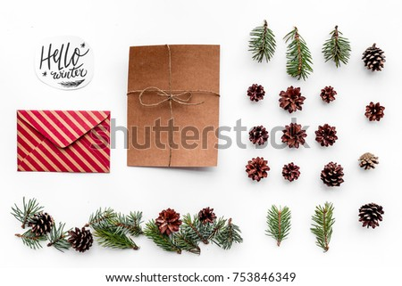 Write greetings. Envelope, paper, spruce branches and cones and hello winter hand lettering on white background top view. #753846349
