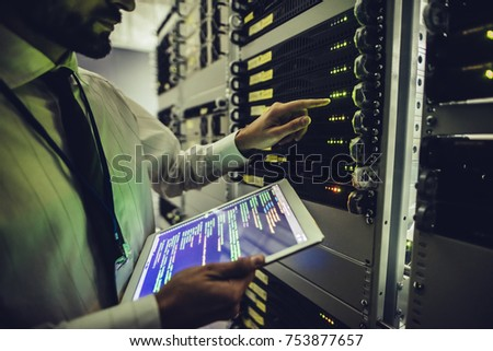 Handsome man is working in data centre with tablet.IT engineer specialist in network server room.Running diagnostics and maintenance.Technician examining server in big data center full of rack servers Royalty-Free Stock Photo #753877657