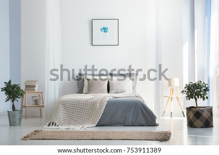 Knit blanket on king-size bed in natural warm bedroom of modern apartment in soft gray and blue colors #753911389
