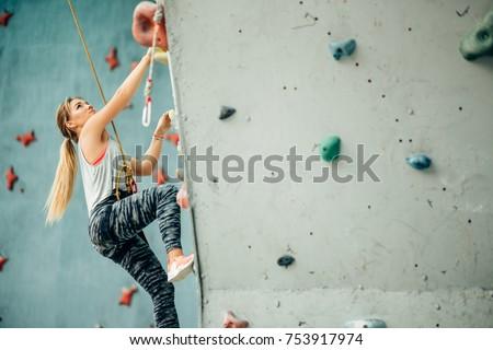 Free climber young woman climbing artificial boulder indoors #753917974