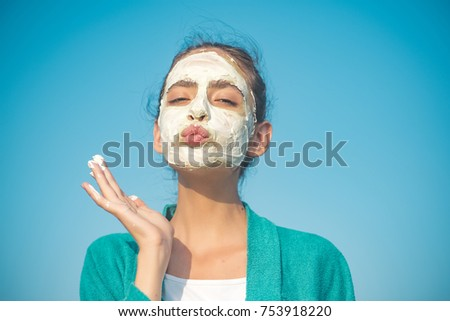 Woman send air kiss with cosmetic mask on face on blue sky. Beauty, nature, youth, skin care, rejuvenation concept #753918220