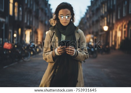 Beautiful young stylish woman walking in the night city streets using modern smartpone, hipster female blogger typing text message on her cellphone