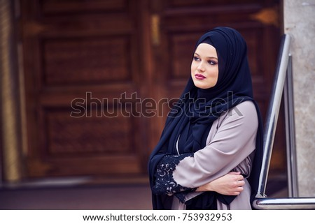 Portrait of a young religious woman wearing hijab in fron of mosque door, islamic #753932953