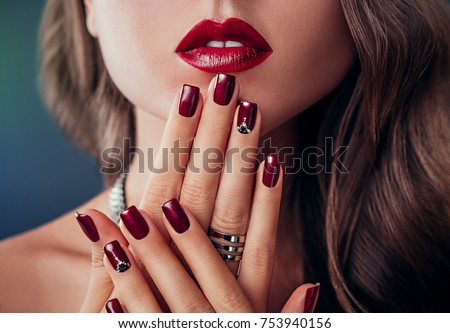 Beautiful woman with red lips and burgundy manicure #753940156