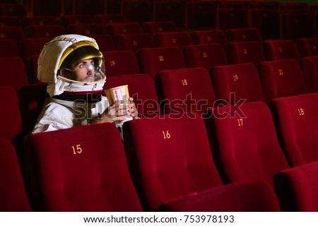 A movie astronaut looks at a movie while eating pop corn and enjoying the movie. Concept of: cinema and space films, film of the other world, surreal situations. #753978193