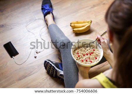 Young girl eating a oatmeal with berries after a workout . Fitness and healthy lifestyle concept. #754006606