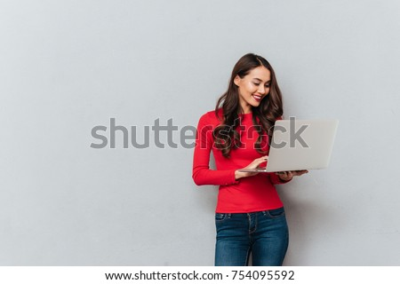 Smiling brunette woman in red blouse using laptop computer over gray background