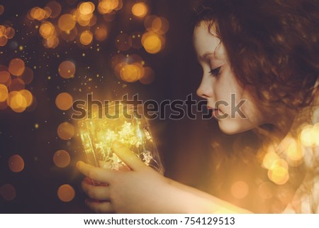 Little girl looking on the magic christmas lamp. New year concept. #754129513