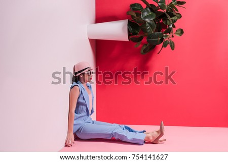 side view of stylish girl in hat and sunglasses sitting upside down in studio #754141627