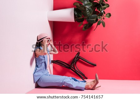 side view of beautiful stylish girl in hat and sunglasses sitting in upside down studio  #754141657