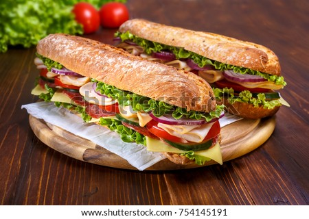 Two baguette sandwiches with salami, turkey breast, cheese, lettuce, tomatoes and onion on a cutting board. Long subway sandwiches on a dark background. #754145191