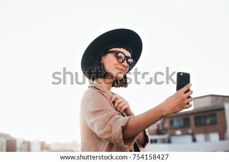 Cute and pretty fashion trendy and hipster millennial woman or girl makes selfie on smartphone camera to share on internet social media channels, self absorbed new generation of young people #754158427