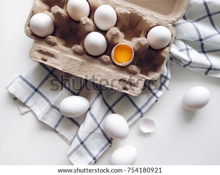 Organic white eggs in package on a kitchen table, egg yolk top view #754180921