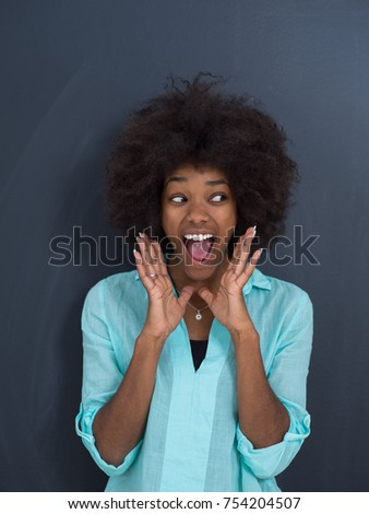 portrait of a beautiful friendly African American woman with a curly afro hairstyle and lovely smile in front of gray chalkboard #754204507