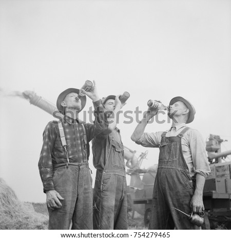 Farmers drinking beer during fall harvest in Jackson, Michigan. Fall 1941. In the background is a potentially dangerous harvesting machine, that requires alert workers. #754279465