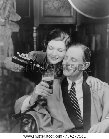 Young woman pouring beer into a man's glass, 1933. Photo was created in response to the legalization of beer with an alcohol content of 3.2% when President Franklin Roosevelt signed the Cullen_Harriso