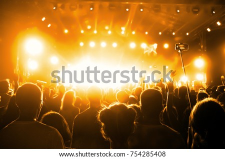 Concert Crowd. Silhouettes young people in front of bright stage lights. Band of rock stars #754285408