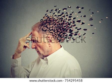 Memory loss due to dementia. Senior man losing parts of head  as symbol of decreased mind function. #754295458