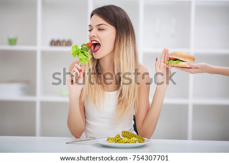 Healthy eating, dieting, slimming and weigh loss concept. Diet. Dieting concept. Weight Loss. The measuring tape is wrapped around the arm. In the other hand is a hamburger. You need to lose weight #754307701