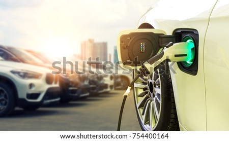 Power supply connect to electric car for add charge to the battery. Charging re technology industry transport which are the future of the Automobile with city background. #754400164